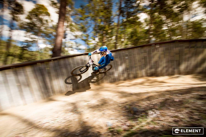 A rider tackles a wooden berm.