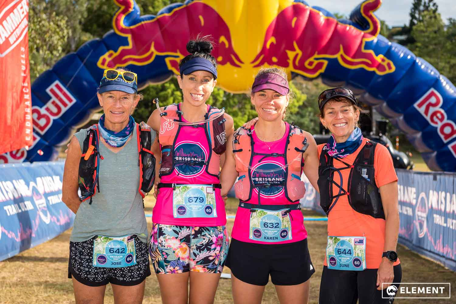 Four participants smiling at the start line of an event.