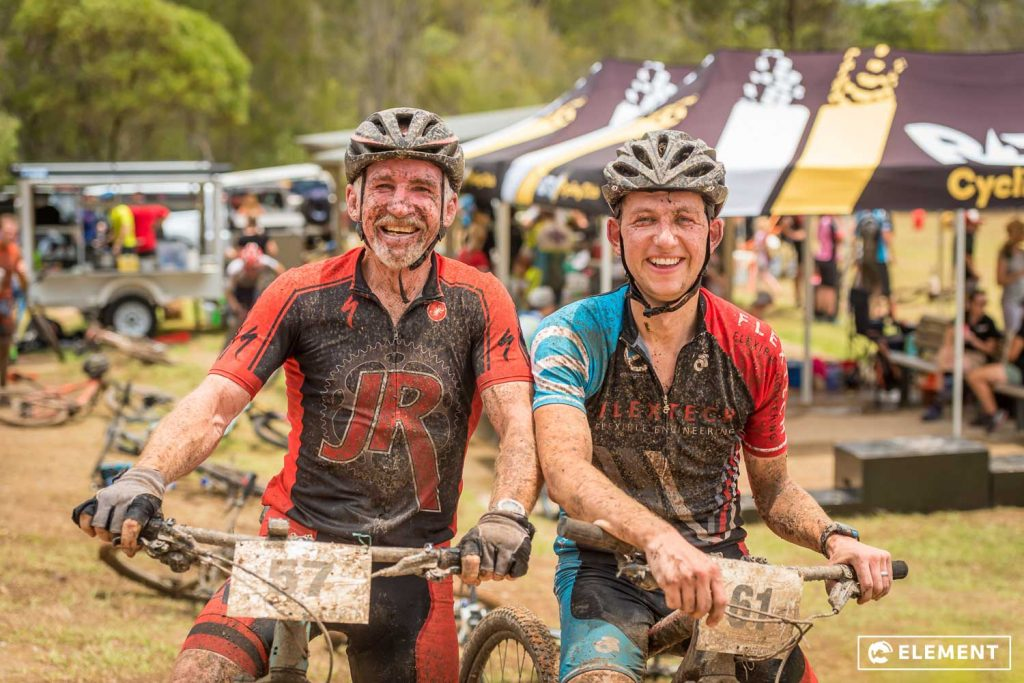 Riders covered in mud,smiling after the race.