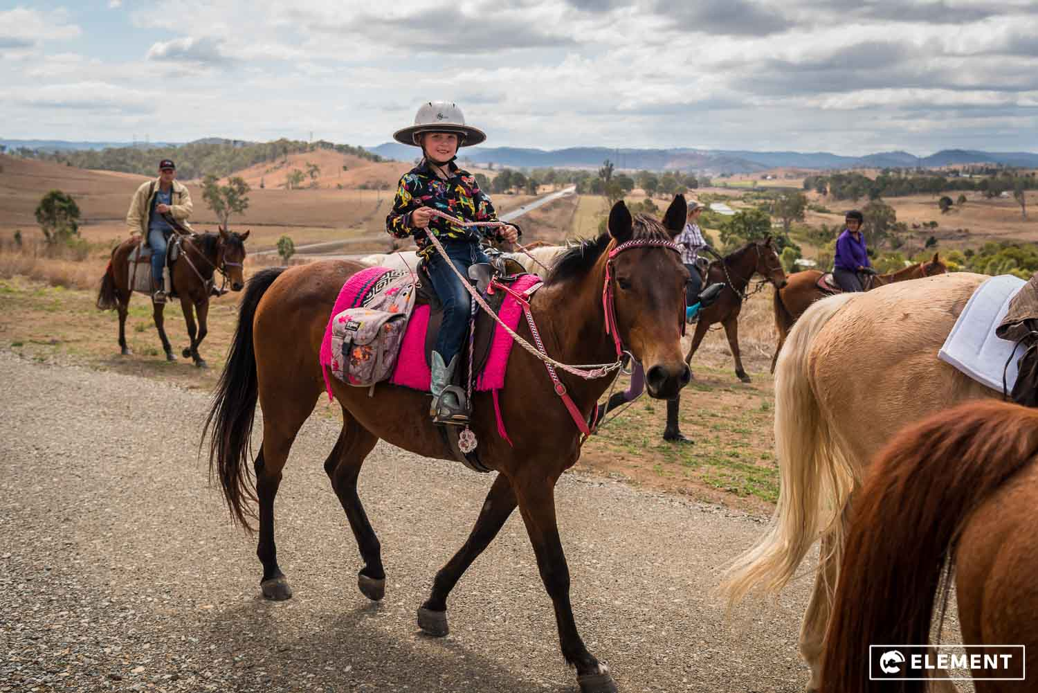 A young girl smiles as she rides her horse.