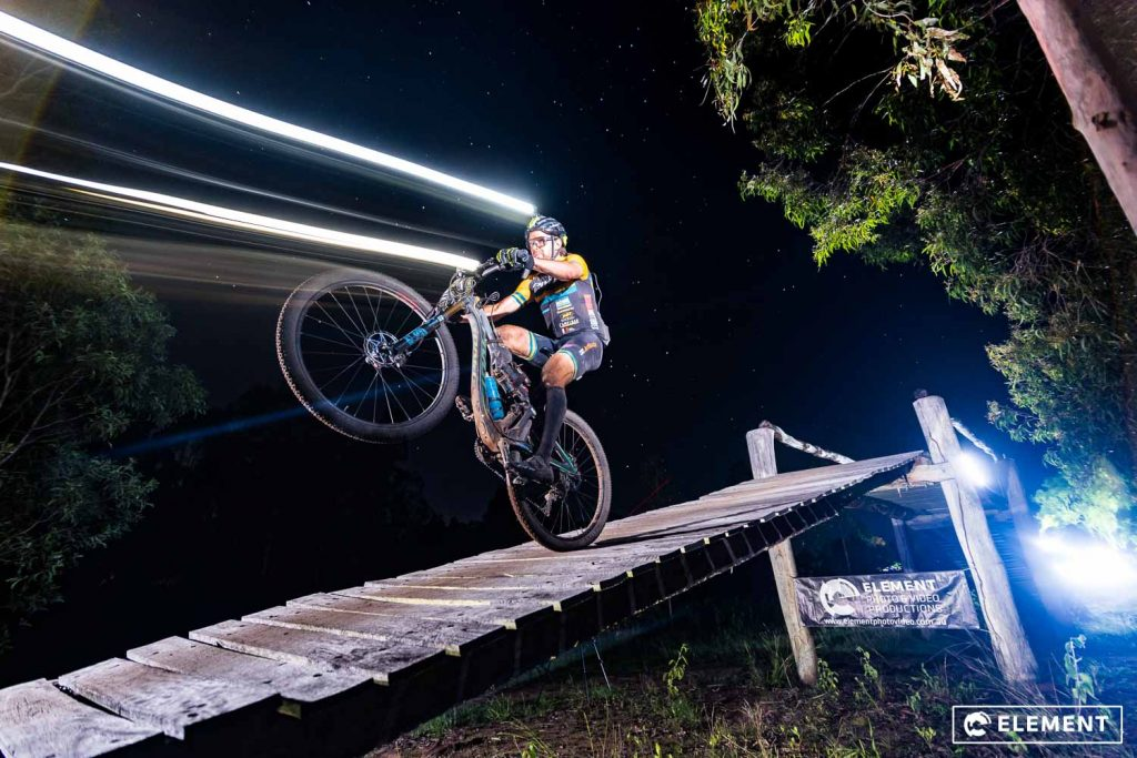 A rider does a wheelie down a ramp in a night race.
