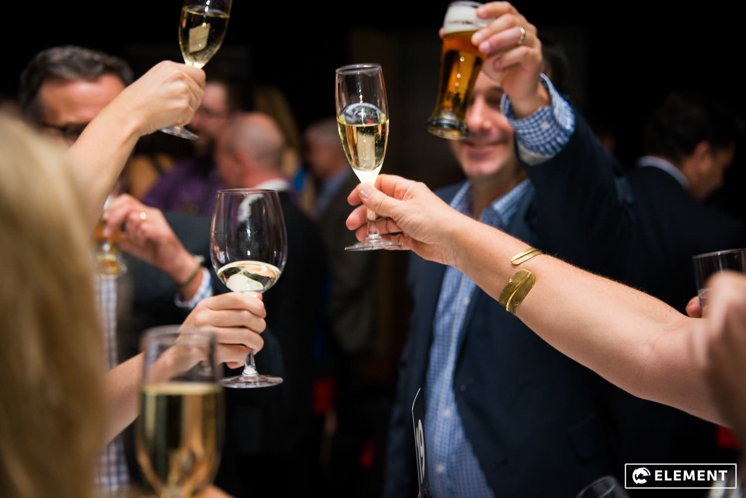 Friends hold up their champagne at an event.